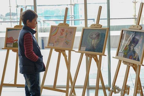 一小朋友正在欣赏澳洲小朋友们的画作