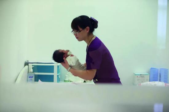 (北京一家高端妇产医院内,医护人员正在照护一名新生儿。 图/视觉中国)