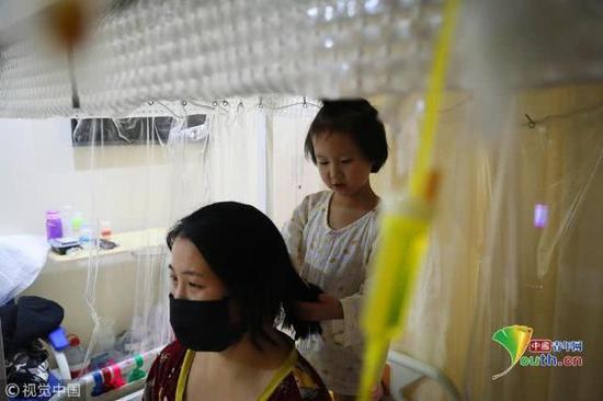 2018年11月17日,北京,住院期间,小娅馨非常懂事地给妈妈梳头。魏建顺/视觉中国
