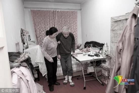 2018年11月22日,辽宁丹东,在出租屋内,袁东方的母亲正在搀扶着老伴儿锻炼身体。魏建顺/视觉中国