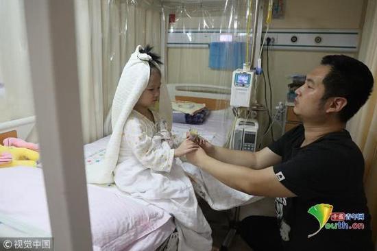 """2018年11月17日,北京,住院期间,4岁的小娅馨披着一条象征着婚纱的毯子坐在床上,爸爸袁东方双手捧着一束小小的假鲜花单膝跪地向女儿""""求婚""""。魏建顺/视觉中国"""