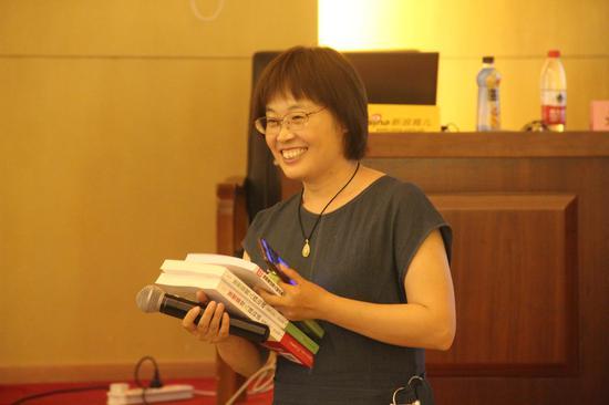 讲座互动环节,工作人员为回答对刘老师提问题的家长送出新浪育儿提供的书一本