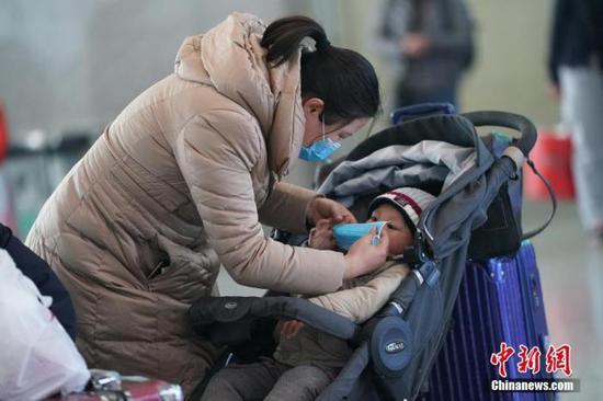 资料图:一名市民为儿童佩戴口罩。中新社记者 张兴龙 摄