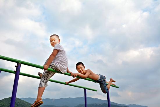 2016年7月,湖北省孝昌县险峰中学的孩子们在操场上玩耍。险峰中学位于大悟山南麓,四面环山,是一所农村寄宿制学校,有小学四年级至初三年级学生近400人。(资料图片)视觉中国供图