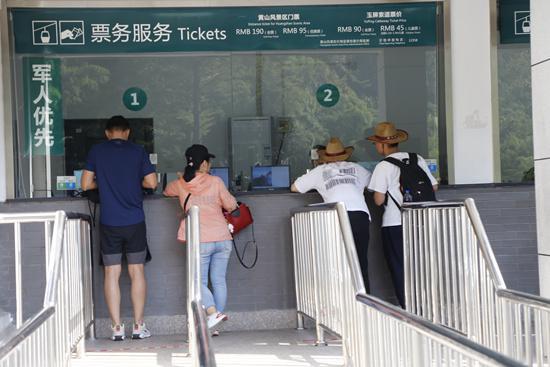 游客在黄山风景区售票处咨询。
