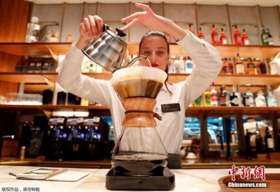 图为一家咖啡店的员工在冲咖啡。