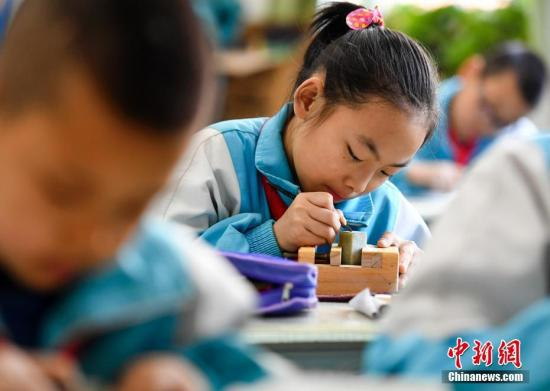 资料图:学生在专业老师的指导下练习篆刻艺术。中新社记者 刘新 摄