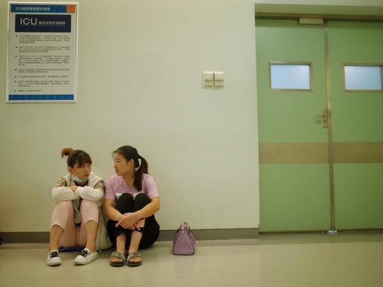 子宽的妈妈和姑姑坐在手术室旁等待子宽手术结束。 新京报记者 陈婉婷 摄