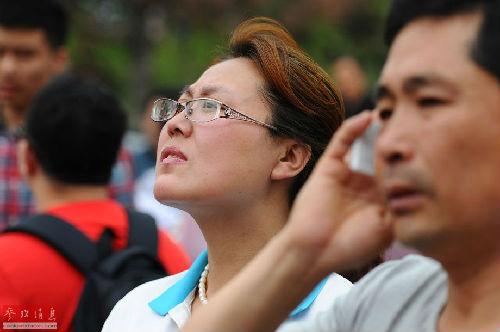 长春市十一高中考点外,家长望向正在进入考场的考生。新华社发