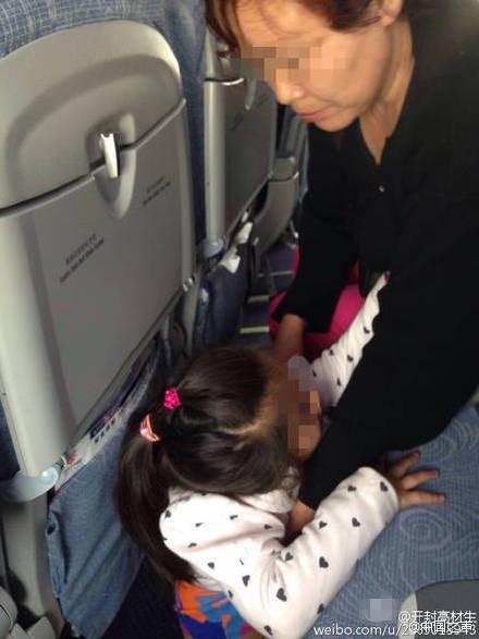 图为老奶奶让孩子在飞机地板上小便。