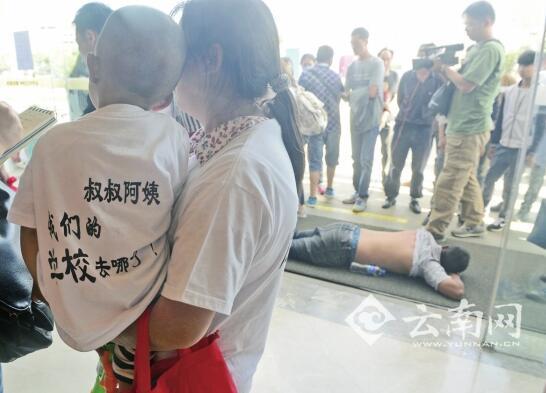 抱着娃娃讨说法,旁边躺着被打伤的业主。