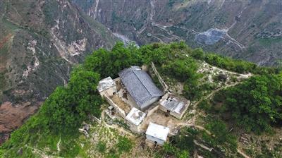 5月13日,无人机俯瞰位于悬崖边缘的村民某色拉则的家,他家的后院门推开就是悬崖,房屋所在位置也是全村最高点。