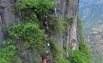 5月14日,在三名家长的保护下,15个孩子从勒尔小学出发,走崖壁,爬藤梯,踏上回家的路。