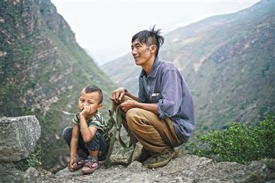 5月14日,爬山开始前,陈古吉用背包绳绕过儿子的胸口,在背后打上结,以确保儿子的安全。