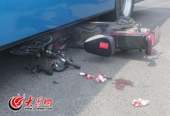 电动车前半部分和男童一起被卷入公交车车底。