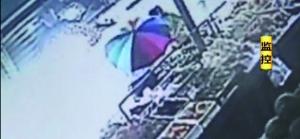 打伞女子挡住摊主视线。视频截图