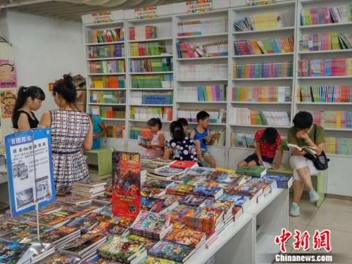 图为暑期家长带着孩子来书店看书。吕春荣 摄
