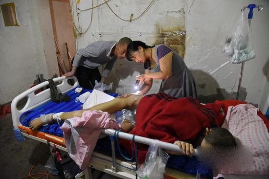 8月22日,冯仕秀给衡林清除腐肉清洗伤口。巴音郭楞日报记者汪涛摄。