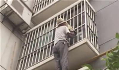 男子托举着卡在防盗窗上的孩子