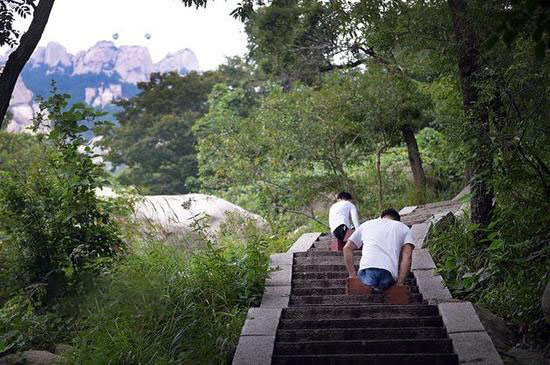 """陡峭的石阶上,两位""""无腿先生""""奋勇攀登"""