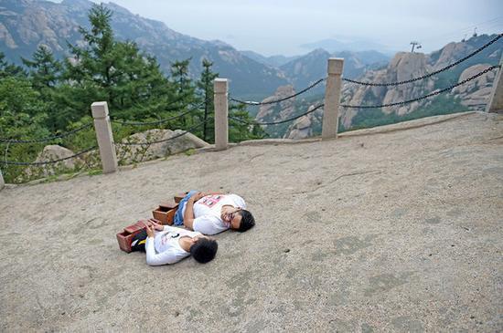 在半山腰的一个平台,他们放下木鞋,躺在石头上享受阳光