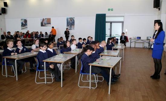 """这是2015年3月17日,在英国伦敦东北部埃塞克斯郡的哈里斯小学,来自中国的数学老师林磊(右一)为三年级的小学生上数学课,教授""""九九乘法表""""在数学计算中的运用。 新华社记者韩岩摄"""