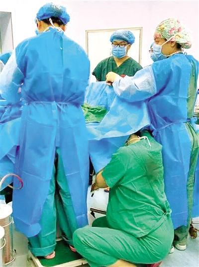 古琳跪在手术床前托举着胎儿头部。