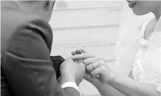 """""""婚礼""""现场儿子为妈妈戴上钻戒。"""