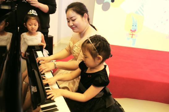欧拉皇家钢琴课老师与小会员展示钢琴表演