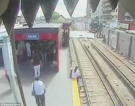 母亲帮助女儿站到了铁轨上以躲避购票,但是忽略了即将进站的火车。