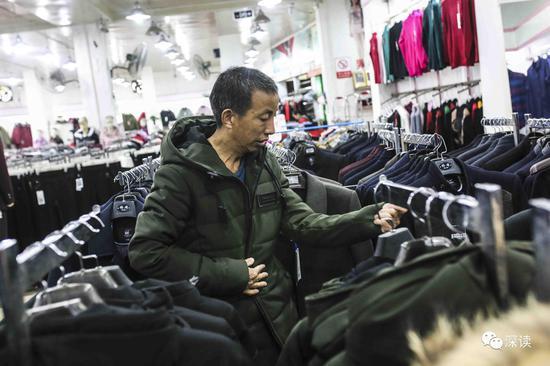 乐建九在商场为身材与自己相当的哥哥乐建作试羽绒服