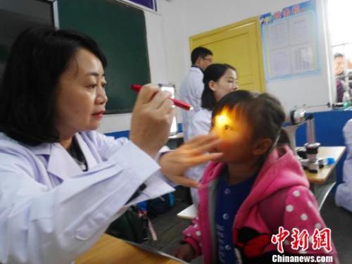 资料图:眼科专家在为山区孩子检查视力。 潘佳 摄