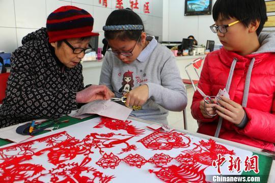 李秀英老人在义务教孩子们学剪纸。李铁锤摄
