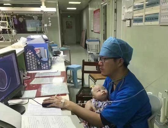 医生边打点滴边哄患儿。