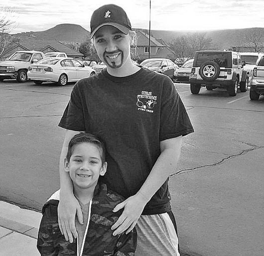 """扮成""""爸爸""""的惠特尼和儿子。为了儿子学校一项要求父亲参加的活动,身为单亲妈妈的她穿上男装,画上胡子,扮成儿子的""""爸爸""""。张文 编译"""