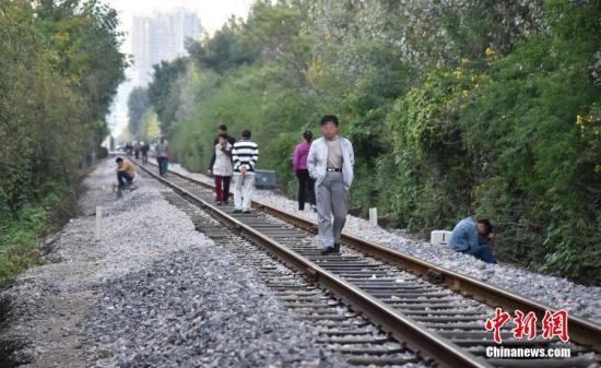 资料图片,市民在铁路上散步。图片来源:CFP视觉中国