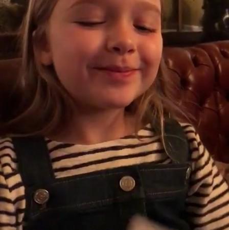 影片中哈珀拿画纸遮脸,用娃娃音轻声哼唱,接着偷偷伸舌头透出画纸,最后露出纯真笑脸,惹得身边众人哈哈大笑。