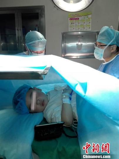 孩子边看动画片边接受手术, 最后还呼呼大睡。 辛丽 摄
