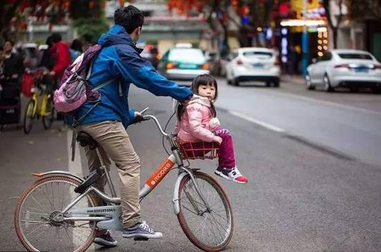 女儿被父亲放在车筐里,父亲正准备过马路。