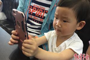 5月14日,天津一家餐厅,一名3岁儿童在等餐期间,用家长的手机聚精会神玩儿游戏。中国青年报</div>             <div id=