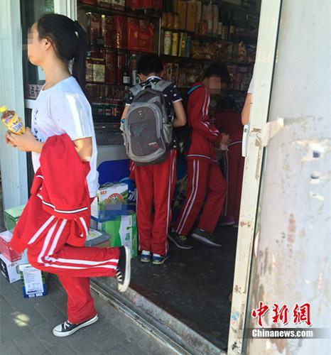 资料图:北京丰台区某小学的学生在附近小超市买东西。中新网 邱宇 摄