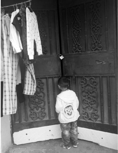 孩子面对大门紧闭的家。