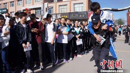 图为内蒙古民警背着受伤考生将他送进考场。 赵晓华 摄