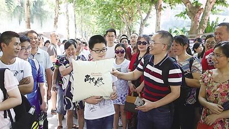 王洪伟(右一)带儿子王瑞丰来现场为考生助威