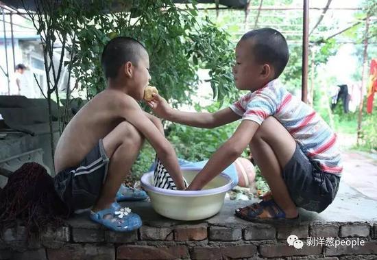 """""""濮阳市艺术公益培训基地"""",一名小朋友在洗衣服,他最好的""""哥们儿""""陪着他,正和他分享一个苹果。"""