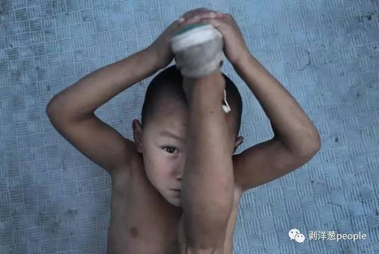 """8月1日,河南""""濮阳市艺术公益培训基地""""。6岁的""""二虎""""正在练习压腿,他是这里年龄最小的。"""