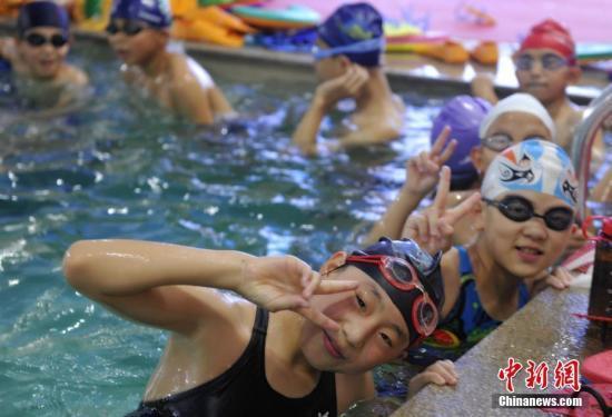 资料图:在某游泳馆避暑的孩子们。中新社记者 韩冰 摄