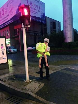 交警给孩子披上雨衣,抱在手上
