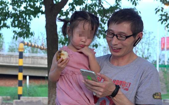司机师傅胡爱松陪依依玩,给她放手机里的动画片。 澎湃新闻记者 朱莹 图