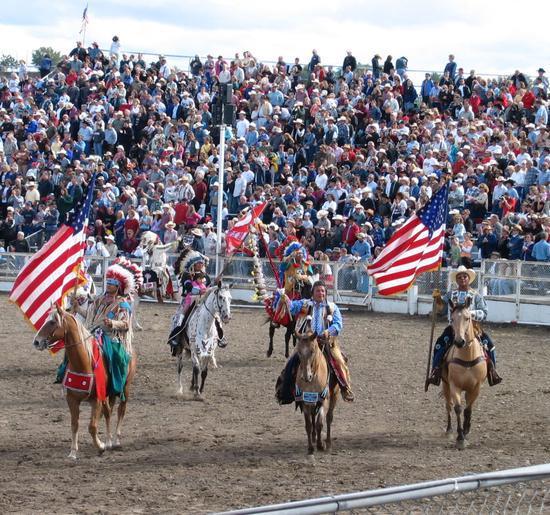 """一场""""牛仔竞技""""前的入场式,参加者高举美国国旗。(图自英文维基百科)"""